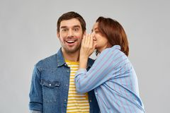 Happy couple whispering over grey background. Secret and people concept - happy couple whispering over grey background royalty free stock images