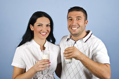 Happy couple in white holding glasses with milk. Happy couple in white clothes standing  in a hug  holding glasses with milk in their hands and smiling,laughing Royalty Free Stock Photography