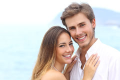 Happy couple with a white smile looking at camera. On holidays on the beach  on white above Stock Image