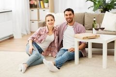 Happy couple with wine and takeaway pizza at home royalty free stock images