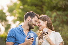 Happy couple with wineglass. At park stock photos