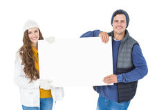 Happy couple in winter clothes holding a poster Royalty Free Stock Images