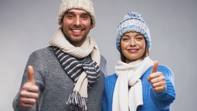 Happy couple in winter clothes showing thumbs up
