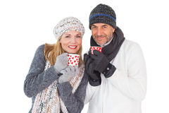 Happy couple in winter fashion holding mugs Stock Photography