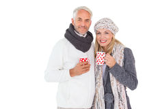 Happy couple in winter fashion holding mugs Royalty Free Stock Image