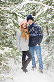Happy couple in winter forest and snowfall among fir trees Stock Photos