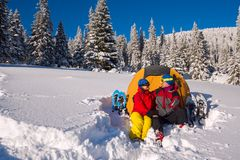 Happy couple during the winter travel in wilderness. Men and a women are sitting next to a tent and hugging, amidst huge snow-covered fir trees. Amazing Stock Photos