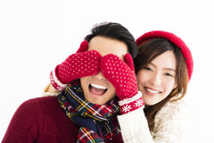 Happy couple in winter wear and covering eyes to surprised Stock Photo