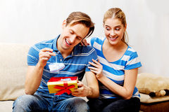 Happy couple - woman hugging her husband who holding gift box and baby shoe Royalty Free Stock Image