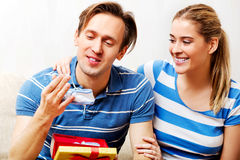 Happy couple - woman hugging her husband who holding gift box and baby shoe Royalty Free Stock Images