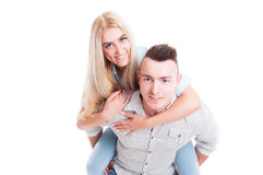 Happy couple with woman piggyback on man Stock Images
