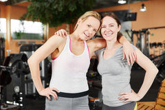 Happy couple of women as friends at the gym Stock Photography