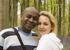 Happy couple in a wood. Young happy ethnically diverse couple in nature Stock Photography