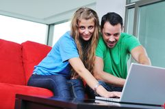 Happy couple work on laptop at home Stock Photography