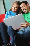 Happy couple work on laptop at home Stock Images