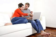 Happy couple working or online shopping on their laptop on sofa Stock Photography