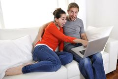 Happy couple working on their laptop on sofa Stock Photos