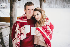 Happy couple wrapped in plaid drink hot tea in a snowy forest Stock Photography