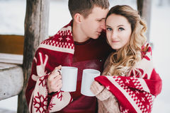 Happy couple wrapped in plaid drink hot tea in a snowy forest. Young happy couple wrapped in a red blanket drinking hot tea in a winter snowy forest Stock Images
