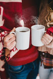 Happy couple wrapped in plaid drink hot tea in a snowy forest. Young happy couple wrapped in a red blanket drinking hot tea in a winter snowy forest Royalty Free Stock Photography
