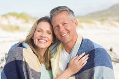 Happy couple wrapped up in blanket Stock Image