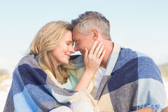 Happy couple wrapped up in blanket Royalty Free Stock Photos
