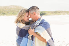 Happy couple wrapped up in blanket Stock Photo