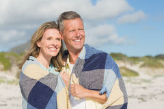 Happy couple wrapped up in blanket Royalty Free Stock Photography