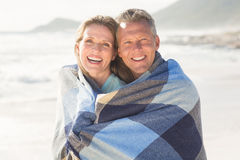 Happy couple wrapped up in blanket Stock Photos