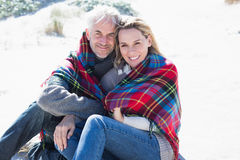 Happy couple wrapped up in blanket sitting on the beach Royalty Free Stock Images