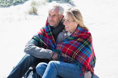 Happy couple wrapped up in blanket sitting on the beach Royalty Free Stock Image
