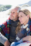Happy couple wrapped up in blanket sitting on the beach Stock Photo