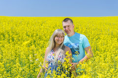 Happy couple in yellow rape field. Beautiful young girl, having fun in flower field on summer day. Just married, young family, spending time together, romantic Royalty Free Stock Photos
