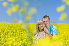 Happy couple in yellow rape field. Beautiful young girl, having fun in flower field on summer day. Just married, young family, spending time together, romantic Stock Photography