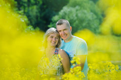Happy couple in yellow rape field. Beautiful young girl, having fun in flower field on summer day. Just married, young family, spending time together, romantic Stock Photos