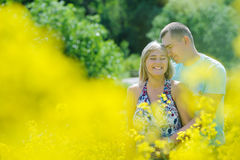 Happy couple in yellow rape field. Beautiful young girl, having fun in flower field on summer day. Just married, young family, spending time together, romantic Royalty Free Stock Images