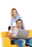 Happy couple on yellow sofa Royalty Free Stock Image
