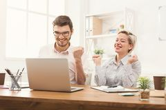 Couple of business partners work at modern office. Happy couple of young business partners working in modern office. Two coworkers discussing new project while Stock Images