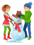 Happy couple of young people sculpts snowman. Merry Christmas. Stock Image