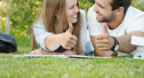 Happy couple of young students studying in the park Stock Images