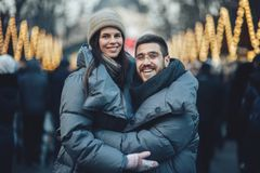 Happy couples on the city square decorated for a Christmas marke Royalty Free Stock Photos