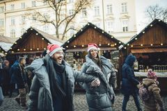 Happy couples on the city square decorated for a Christmas marke Stock Photo