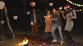 Happy couples and friends celebrating new years eve with sparkler and dancing stock video