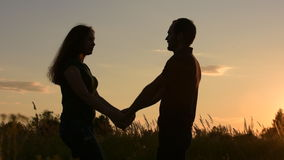 Happy couples go to meet each other. Side view under direct sunlight. At sunset. stock video