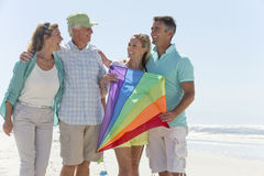 Happy couples with kite on sunny beach royalty free stock photography