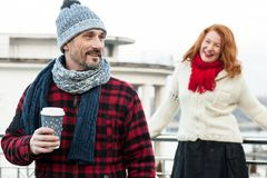 Happy couples loves coffee. Smiling guy holds craft cup with coffee hiding from girlfriend behind. Man with coffee and girlfriend stock photography