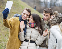 Happy couples taking self portrait through cell phone in park Royalty Free Stock Image