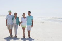 Happy couples walking on sunny beach Stock Photography