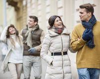 Happy couples in warm clothing enjoying vacation Stock Photos