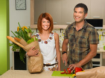 Happy couplestanding in kitchen and cooking Stock Photos